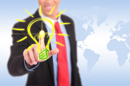 save electricity: smiling business man pushing a light bulb button having a great idea Stock Photo