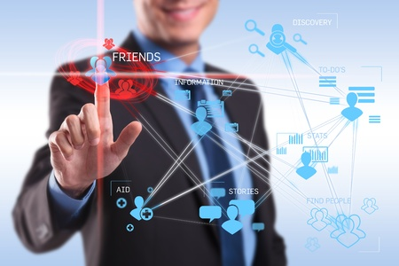 social relation: business man pushing the friends button on a social network application screen Stock Photo