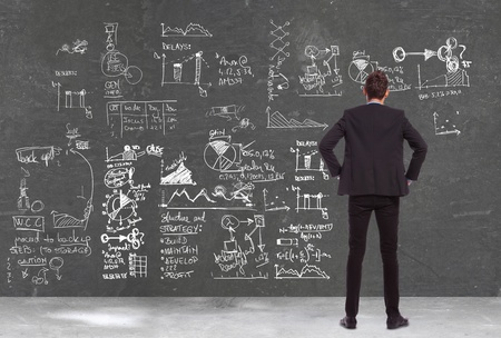 back view of a business man  looking at some charts , graphs and calculations on a blackboard  photo