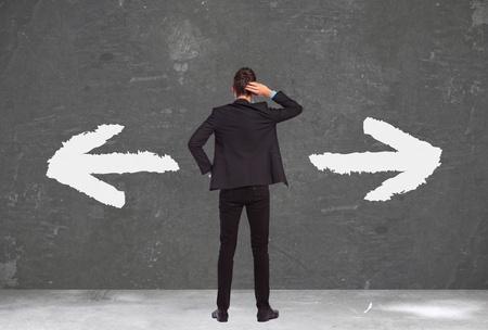 ind�cis: dos d'un jeune homme d'affaires ind�cis debout, la main sur sa t�te et la pens�e de faire waht