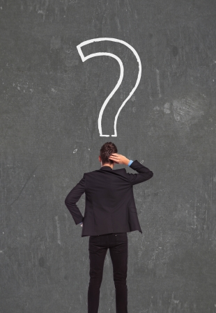 road mark: Confused, young businessman looking at question mark