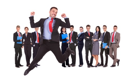 business man jumping in front of his business team formed of young businessmen and businesswomen standing over a white background  photo