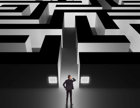 labyrinth: Business man in front of a huge maze thinking how to get through Stock Photo