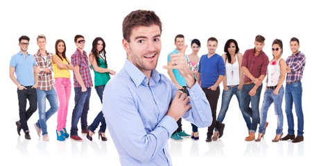 casual young man making the call me hand gesture in front of a large group of casual fashion people Stock Photo - 17449628