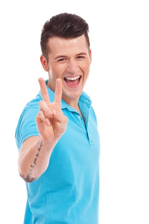 victory stand: Portrait of young man smiling and showing you victory sign on white background