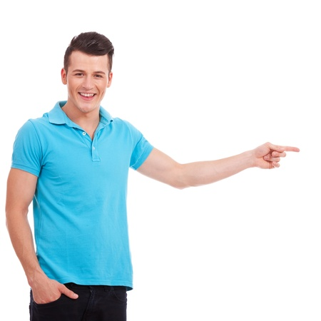 polo shirt: Happy casual young man showing something and looking at the camera, isolated over a white background