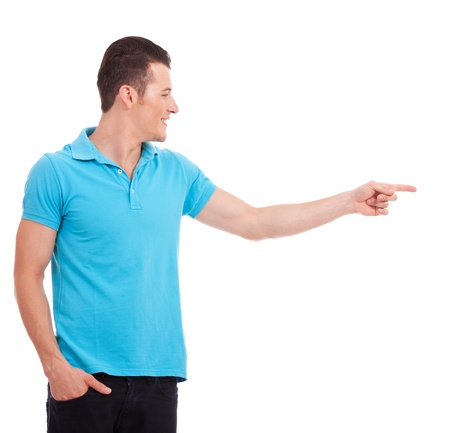 hand gestures: Casual young man pointing and looking to his side, with the other hand in his pocket, over white background  Stock Photo