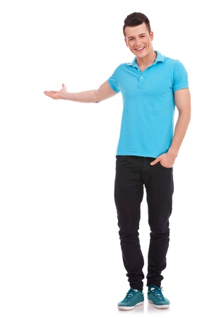 blue shirt: Young casual man is presenting something while holding his other hand in his pocket and smiling to the camera on white Stock Photo