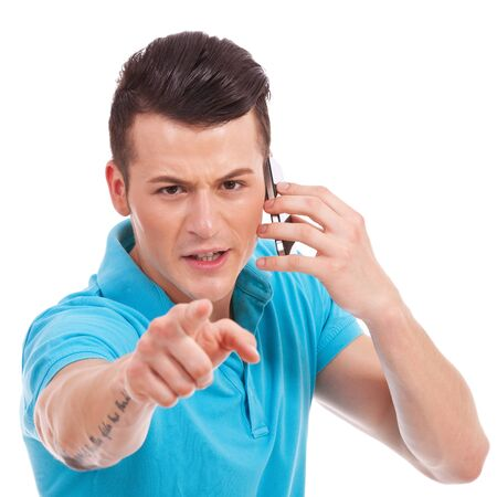 waistup: waist-up picture of an attractive young casual man pointing and looking angrily at the camera while speaking on the phone