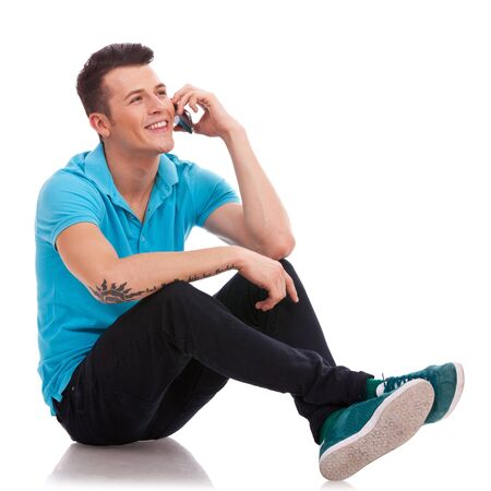 man legs: Appealing young casual man speaking on the phone and sitting with his legs crossed. He is looking somewhere up and smiling Stock Photo