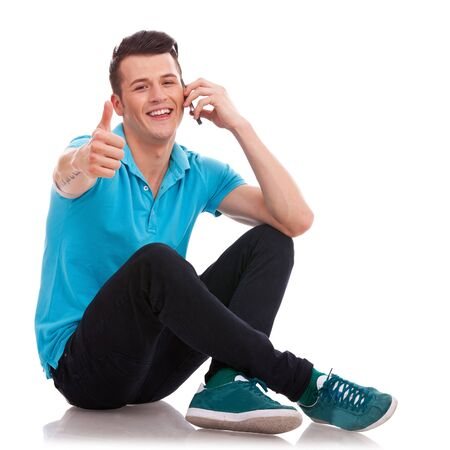 appealing: Appealing casual young man sitting with his legs crossed and showing thumbs up sign, while speaking on the phone and smiling to the camera. Isolated on white background