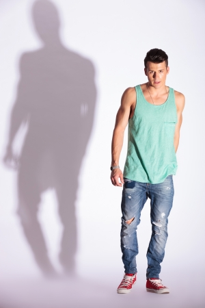 young fashion man looking at the camera and standing on white background with hard shadow  photo