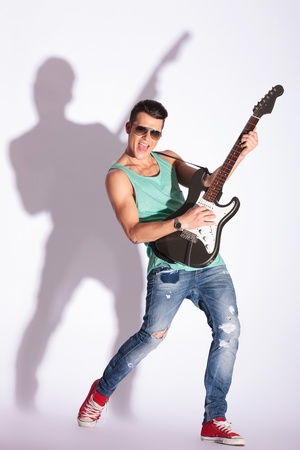 young guitarist model playing on electric guitar and shouting, while looking at the camera, on a gray background with hard shadow photo