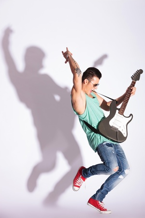 full length photo of a young casual fashion man practicing his rock on an electric guitar, against gray background and hard shadow photo