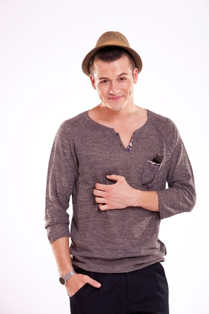 waste-up picture of a young casual man scratching his belly and holding a hand in his pocket, while looking at the camera, on a light background photo