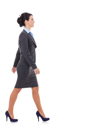 Side view of a business woman walking isolated over a white background photo