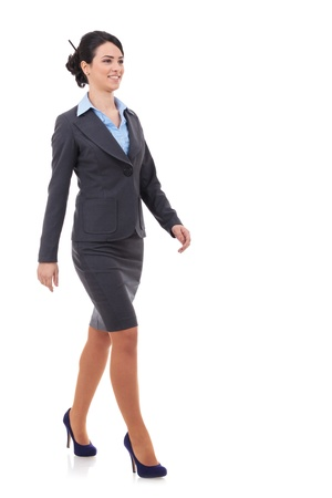 midlife: young business woman is walking. She is smiling and looking away from the camera isolated over white background
