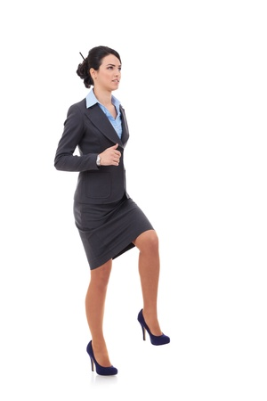 elegant staircase: Young attractive business woman stepping on imaginary step and looking away from the camera, upwards, suggesting progress