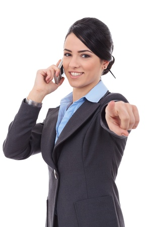 Smiling business woman talking on mobile phone and pointing finger at you photo