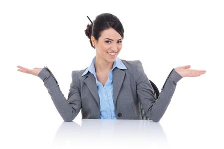 arms wide: donna d'affari giovane seduto dietro la scrivania ed accogliente voi con un bel sorriso sul suo volto e le braccia spalancate. isolato su bianco Archivio Fotografico