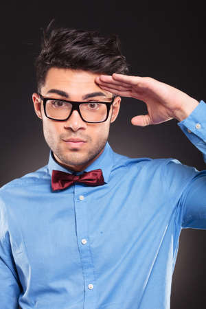 casual fashion man making a military salute on dark background  photo