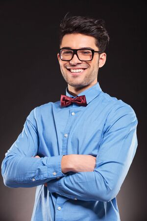 Portrait of young casual man with glasses smiling on dark background photo
