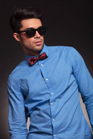 fashion shot of an elegant young man wearing suit, bow tie and sunglasses looking away from the camera Stock Photo - 17449632