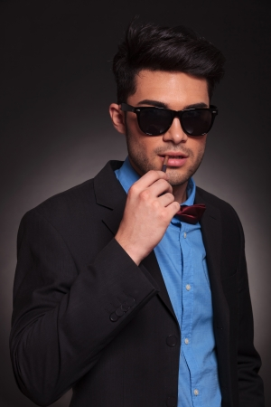 young fashion man with sunglasses ready for smoking a cigarette photo