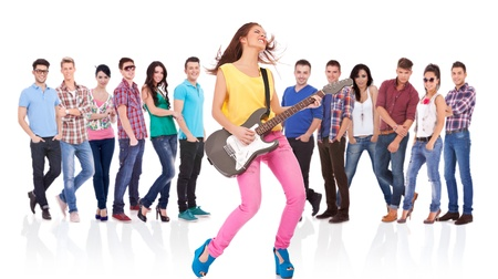 passionate woman guitarist playing rock and roll on her guitar in front of large group of friends Stock Photo - 17449670