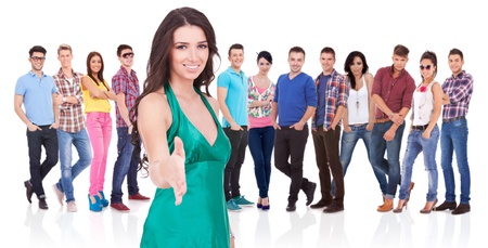 young casual woman welcoming you with a handshake in front of her large team Stock Photo - 17449659