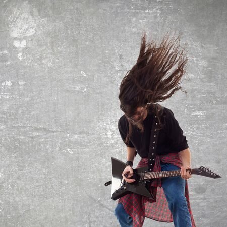 harmonist: headbanging electric guitar player on gray background playing the rock music