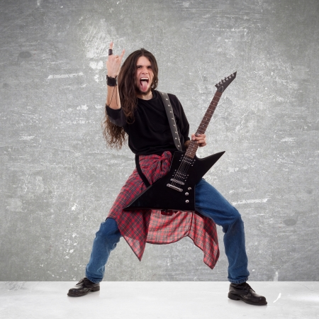 loud music: long haired guitarist is playing and making a rock hand gesture Stock Photo