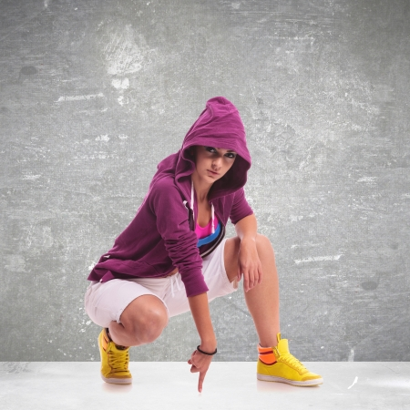 to crouch: young hip hop woman dancer wearing a hoodie, posing crouched and touching the floor