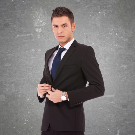 picture of a srious young business man buttoning his coat Stock Photo - 17624978