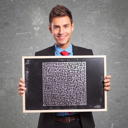 cartel: Young business man holding a blackboard with a drawn maze
