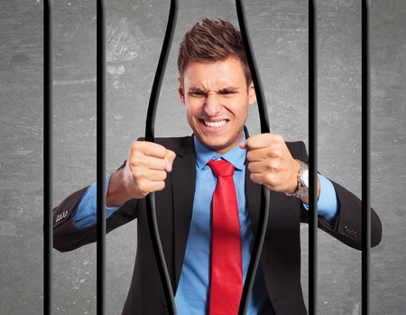 escape: angry strong businessman bending the bars of his prison trying to get out