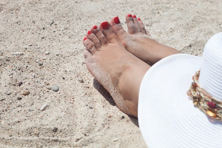 tiptoe: red nailed toes of a woman sunbathing on the beach