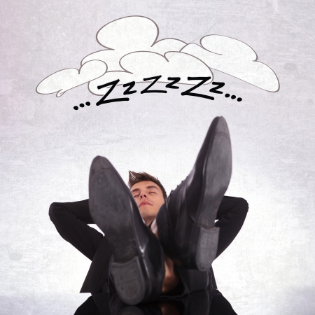 day dreaming: tired business man sleeping with his legs on his office desk