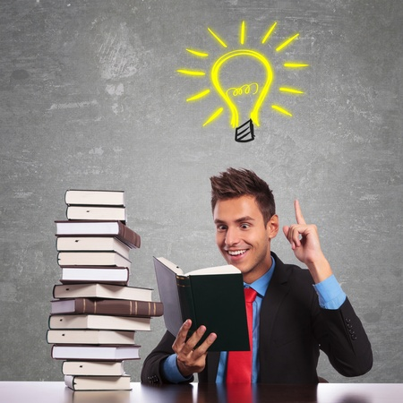 young business man having a great idea while reading an interesting book photo