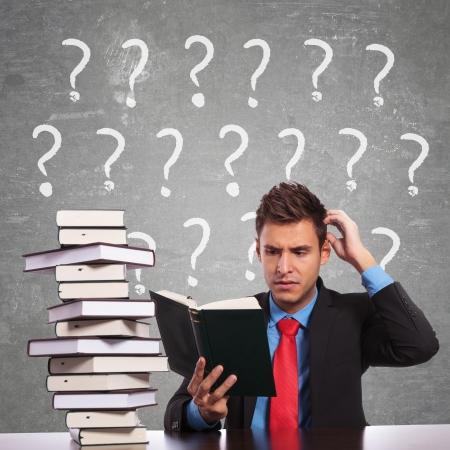 혼란스러운: 책을 읽는 동안 그의 머리를 긁 혼란 된 비즈니스 사람 스톡 사진