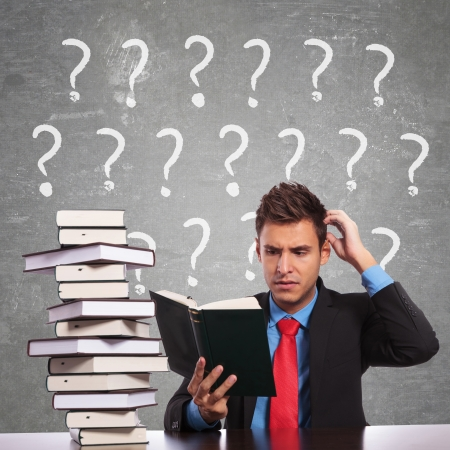examination stress: confused business man scratching his head while reading a book Stock Photo
