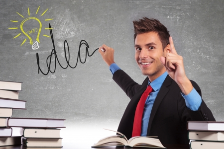 new idea: young business drawing a light bulb on his black board meaning he is having a great idea