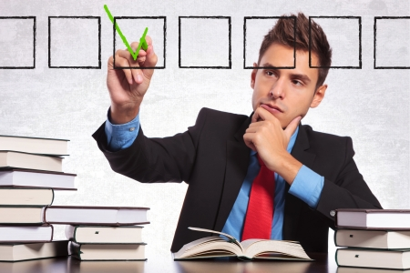 answer approve of: business man at his desk checking on a list of books that he read