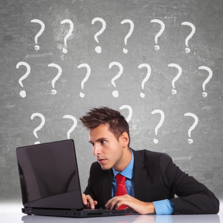 confused person: hombre de negocios curioso mirando la pantalla del ordenador port�til y tener un mont�n de preguntas Foto de archivo