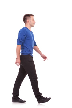 side view of a young casual man walking forward photo