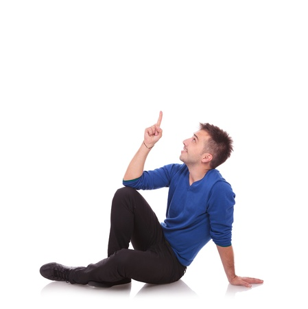 man pointing up: young casual man sitting on the floor, pointing and looking upwards while smiling. on white background