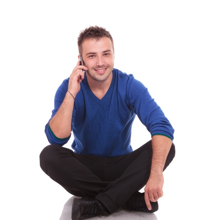 legs folded: Appealing young casual man speaking over the phone and sitting with his legs crossed. He is looking at the camera and smiling Stock Photo