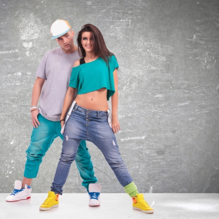 couple of young man and woman  hip-hop dancers, posing at studio. photo