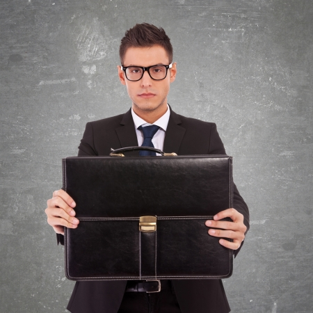 serious business man wearing glasses, offering a briefcase to you on gray background photo