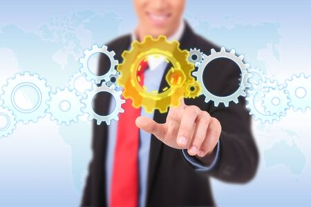 business man pushing a cog button on a word map background photo